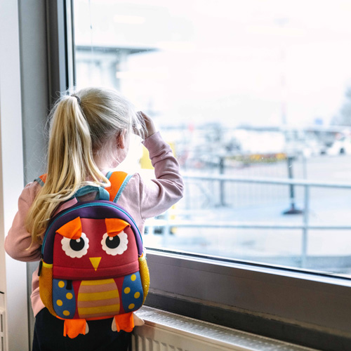 Child looks out of the window at the airport